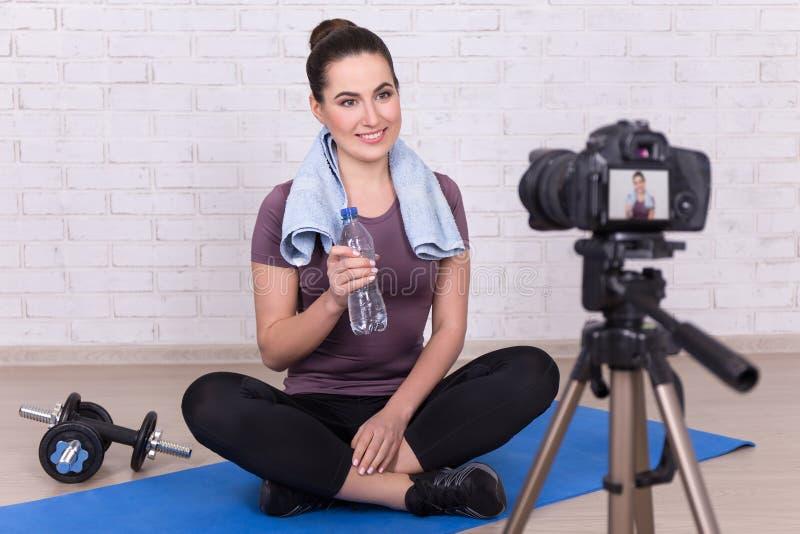 Blogger deportivo joven de la mujer que hace el nuevo vídeo en casa imagenes de archivo
