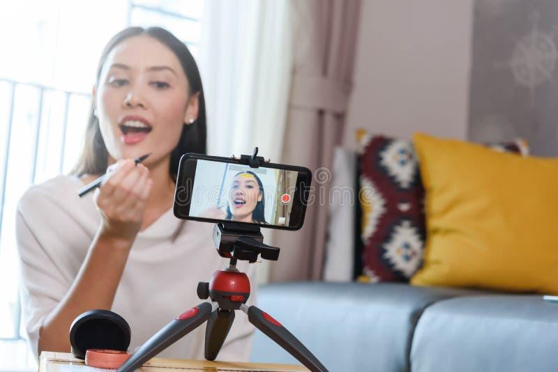 Blogger di bellezza che dimostra come applicare eye-liner ed esaminare i prodotti sulla radiodiffusione in tensione per i media s immagine stock