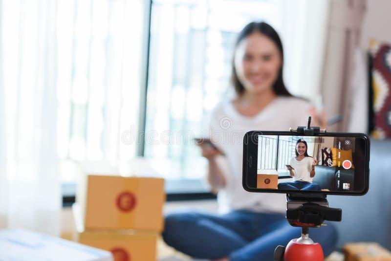Blogger di bellezza che dimostra come comporre ed esaminare i prodotti sullo smartphone di uso di radiodiffusione in tensione fotografia stock