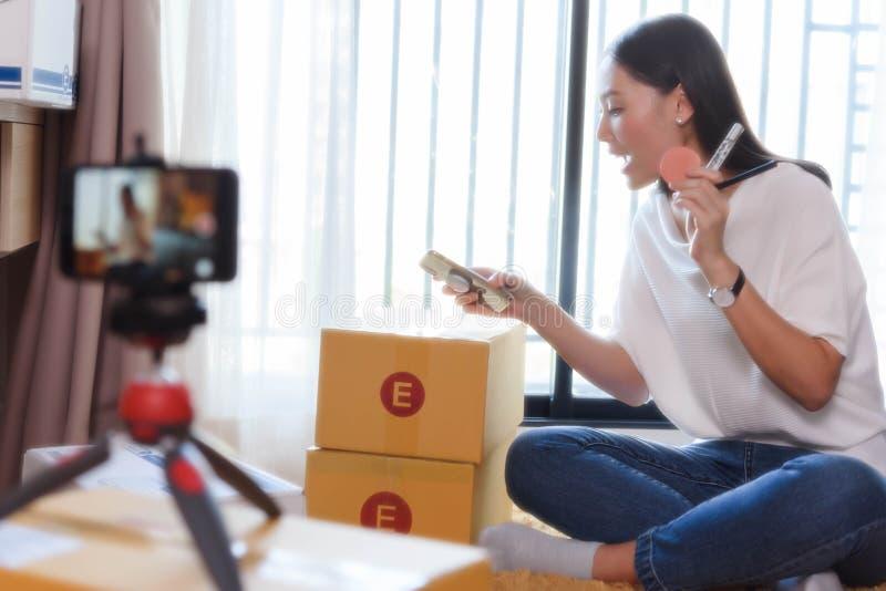 Blogger di bellezza che dimostra come comporre ed esaminare i prodotti sullo smartphone di uso di radiodiffusione in tensione fotografie stock