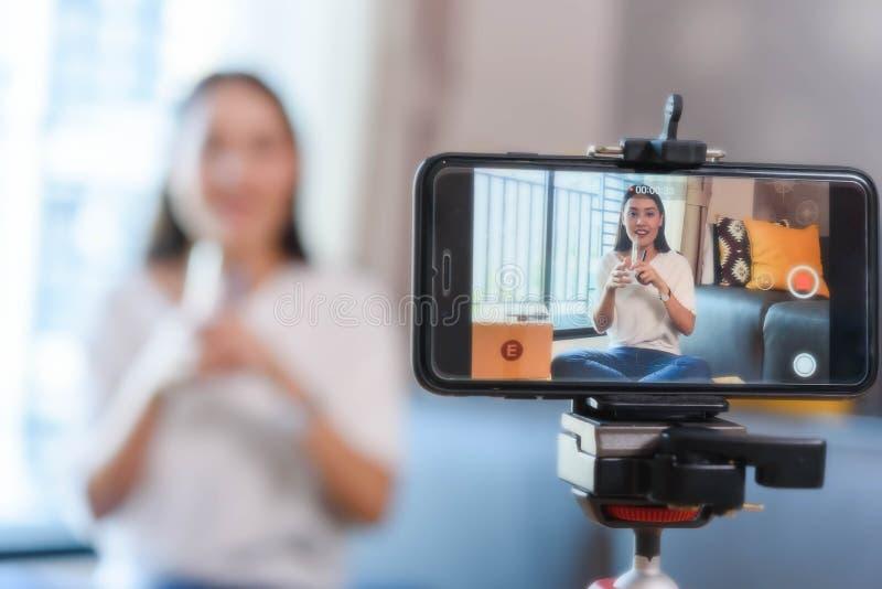 Blogger di bellezza che dimostra come comporre ed esaminare i prodotti sullo smartphone di uso di radiodiffusione in tensione immagini stock