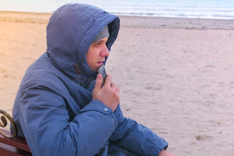 Blogger do homem em um azul abaixo do revestimento que senta-se em um banco na praia da areia e que escreve um cargo em meios soc imagens de stock royalty free