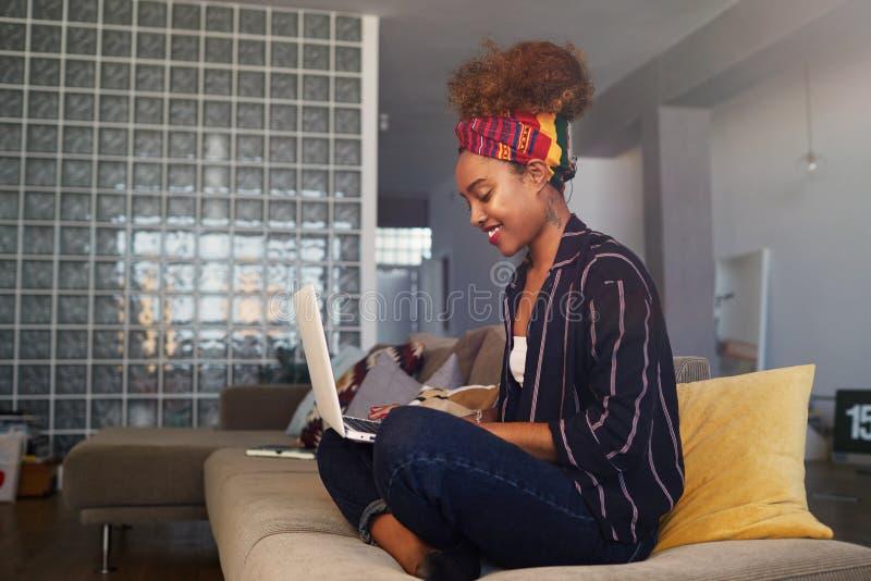 Blogger féminin africain de jeune Américain travaillant à distance sur le netbook numérique avec le texte d'Internet Redacteur pu images libres de droits