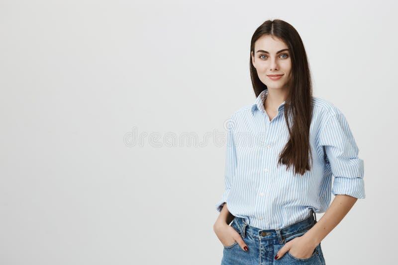 Blogger fêmea novo bem sucedido que está com mãos no bolso e que olha a câmera com olhar seguro e agradável fotos de stock