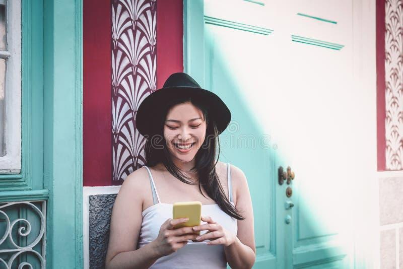 Blogger feliz de la moda de Asia que usa el teléfono móvil al aire libre - muchacha china que se divierte con los nuevos apps del foto de archivo