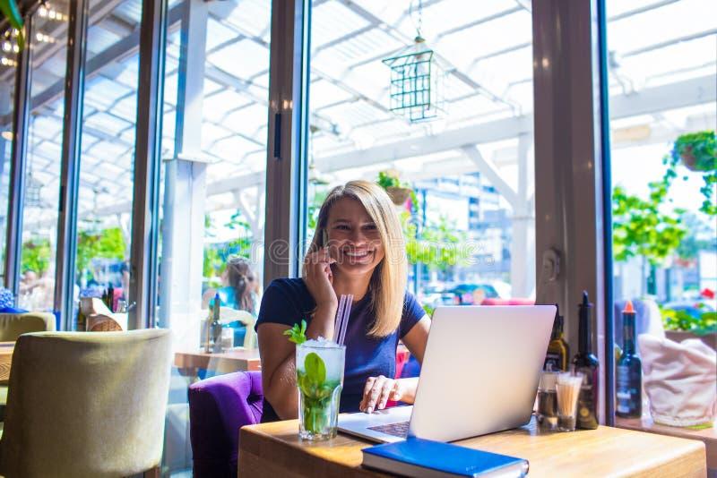 Blogger femenino alegre que tiene conversación agradable vía el teléfono de célula durante el desayuno en café imagenes de archivo
