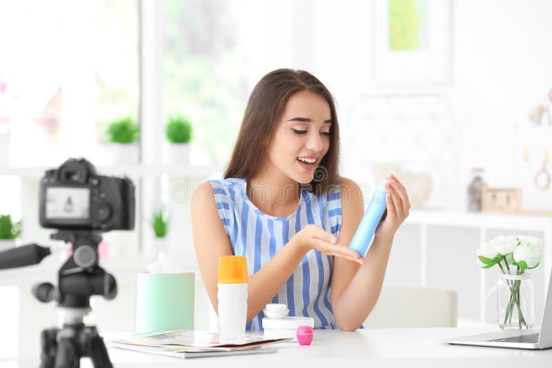 Blogger femenino joven con los cosméticos que registran el vídeo imagen de archivo libre de regalías