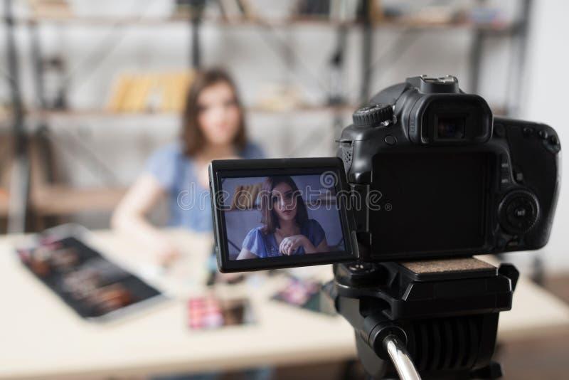 Blogger femenino joven de la belleza en la pantalla de la cámara fotografía de archivo libre de regalías