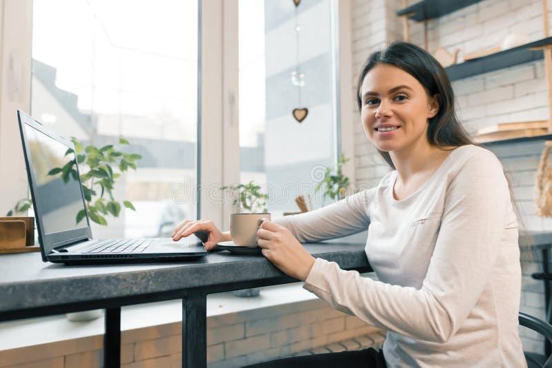 Blogger femenino joven en cafetería con el ordenador portátil fotografía de archivo