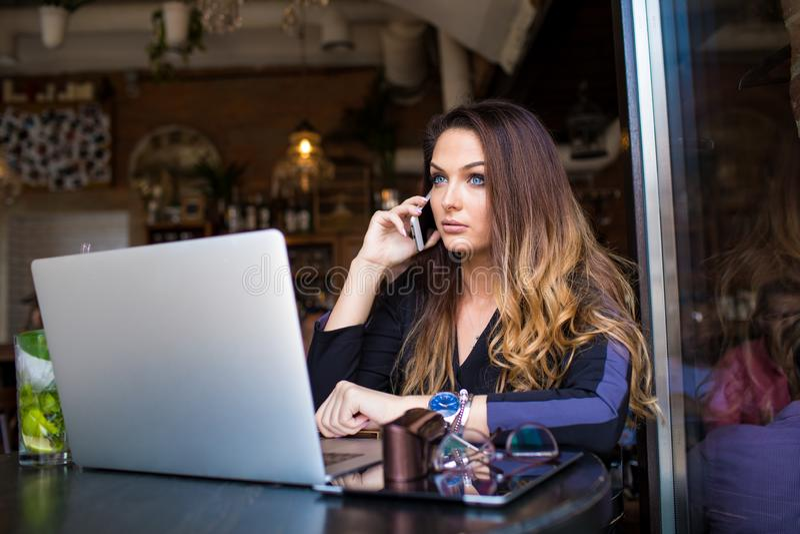 Blogger femenino que habla vía el teléfono de célula durante webinar en línea vía netbook imagen de archivo libre de regalías
