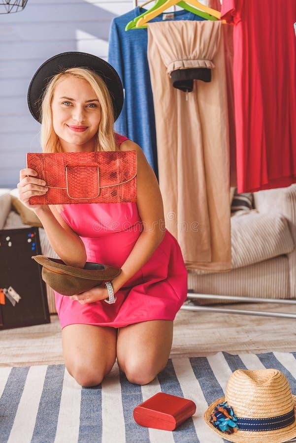 Blogger femminile allegro che mostra piccola borsa immagine stock libera da diritti
