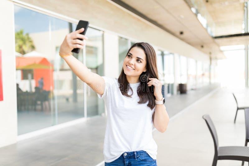 Blogger femminile sorridente che prende Selfie facendo uso di Smartphone immagine stock libera da diritti