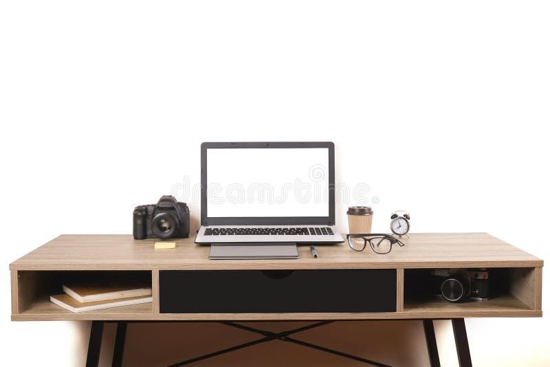 Blogger/fotógrafo/ele da foto tabela típica do espaço de escritórios do ` s do especialista com portátil, a tela vazia, o copo de imagens de stock royalty free