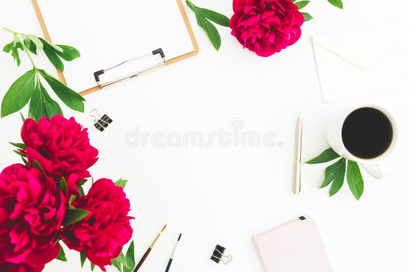 Blogger or freelancer workspace with clipboard, dairy, peony flowers and coffee mug on white background. Flat lay, top view. Beaut. Y blog concept royalty free stock images