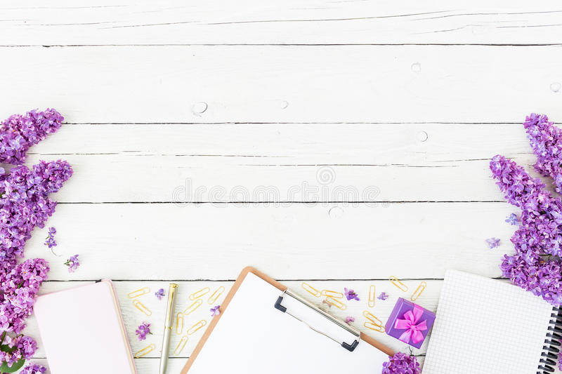 Blogger or freelancer workspace with clipboard, notebook, pen, lilac, box and petals on wooden background. Flat lay, top view. Bea. Blogger or freelancer royalty free stock photo