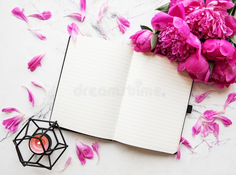 Blogger or freelancer workspace. Flat lay blogger or freelancer workspace with a notebook, pink peonies on a marble background stock images