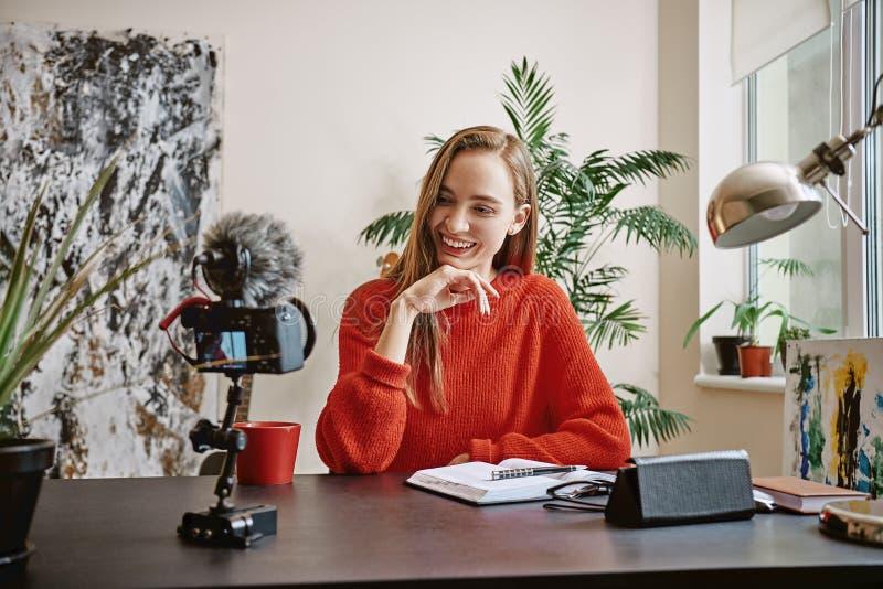 Blogger hermoso Vlogger joven femenino que registra los medios sociales video y que sonríe mientras que mira la cámara imagen de archivo libre de regalías