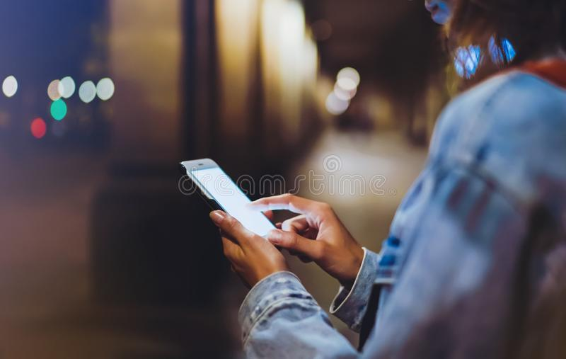 Blogger hipster using in hands gadget mobile phone, woman with backpack pointing finger on blank screen smartphone on background b. Okeh light in night stock image