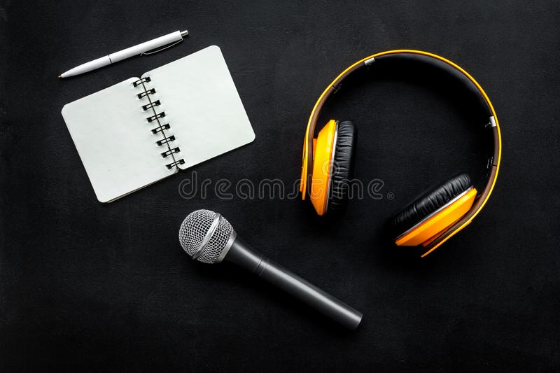 Blogger, journalist or musician office desk with notebook, microphone and headphones on black background top view stock photos