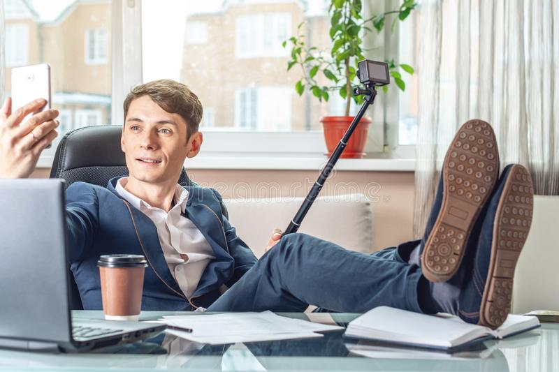 Blogger man businessman recording vlog video in office. Social marketing and online business training. Blogger man businessman recording vlog video in office stock image