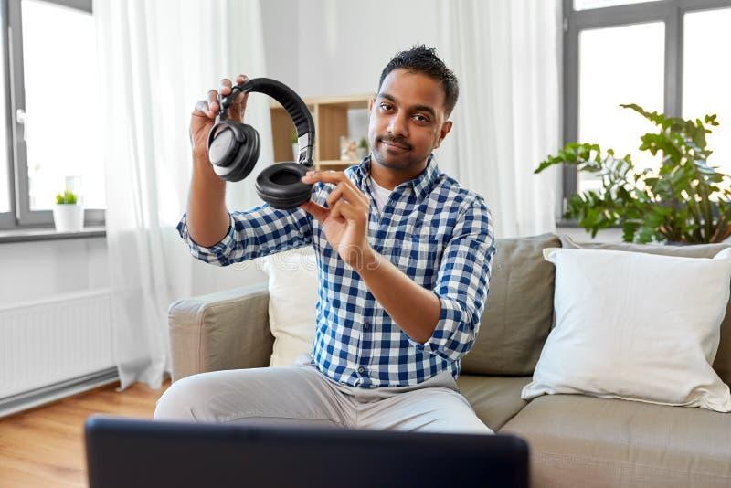 Blogger masculin avec des ?couteurs videoblogging ? la maison images libres de droits
