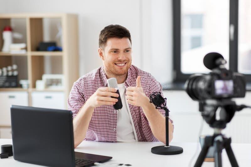 Blogger masculino con el micrófono videoblogging imagen de archivo
