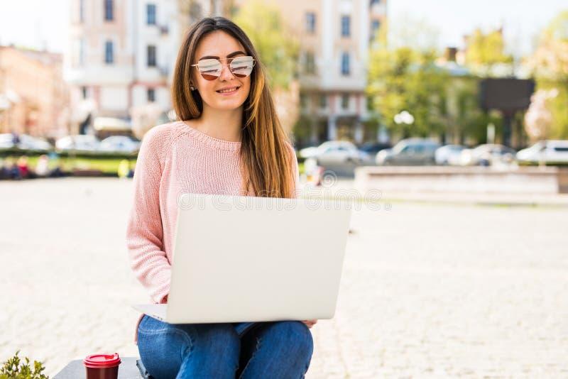 Blogger moderno Vista lateral de la mujer joven hermosa en gafas de sol usando su ordenador portátil y mirada lejos con sonrisa m imagen de archivo libre de regalías