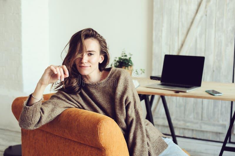 Blogger ou mulher de negócios bem sucedida nova que trabalham em casa em linha com portátil e xícara de café na manhã imagem de stock