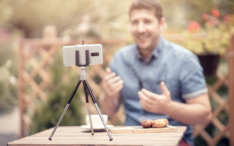 Blogger que fala e que gesticula na frente da câmera Foco seletivo no telefone esperto montado em um tripé Homem que faz o youtub fotografia de stock royalty free