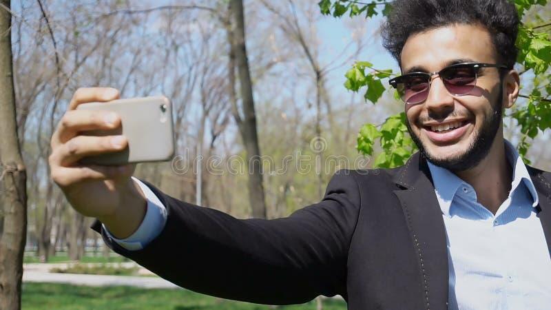 Blogger que faz o vídeo no telefone novo e que mostra o manuseio acima e o pe fotos de stock