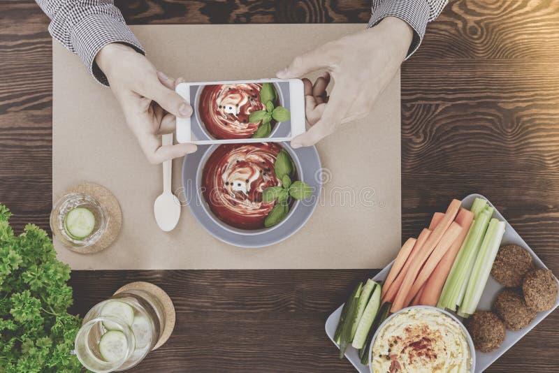Blogger que fotografía la comida sana del vegano imagenes de archivo
