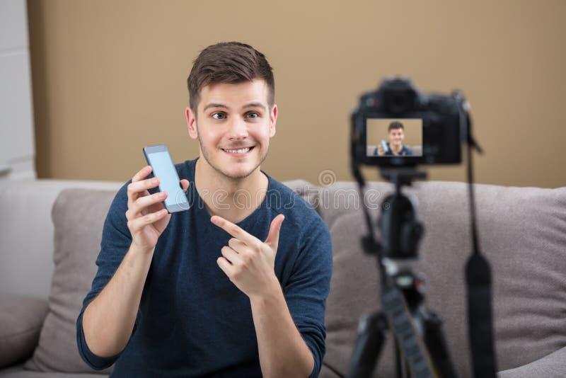 Blogger que lleva a cabo la grabación del teléfono móvil video con la cámara imagenes de archivo