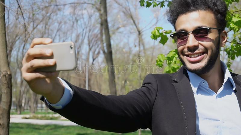 Blogger robi wideo na nowym telefonie i pokazuje thumbing, up pe i zdjęcia stock