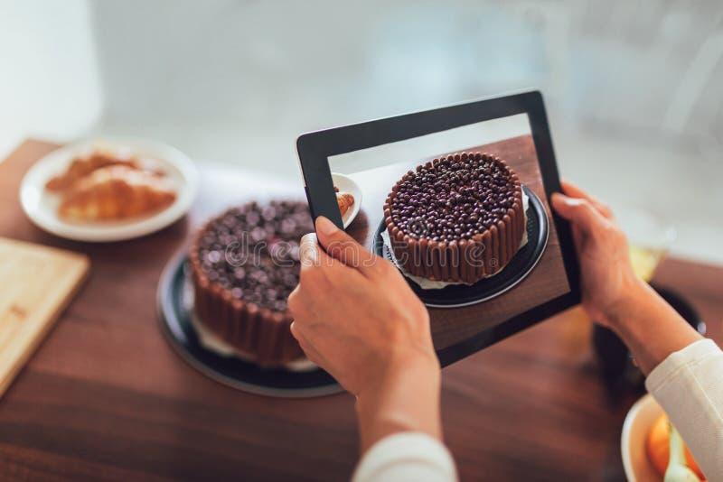 Blogger som tar bilden av kakan för att ladda upp på websiten arkivbild