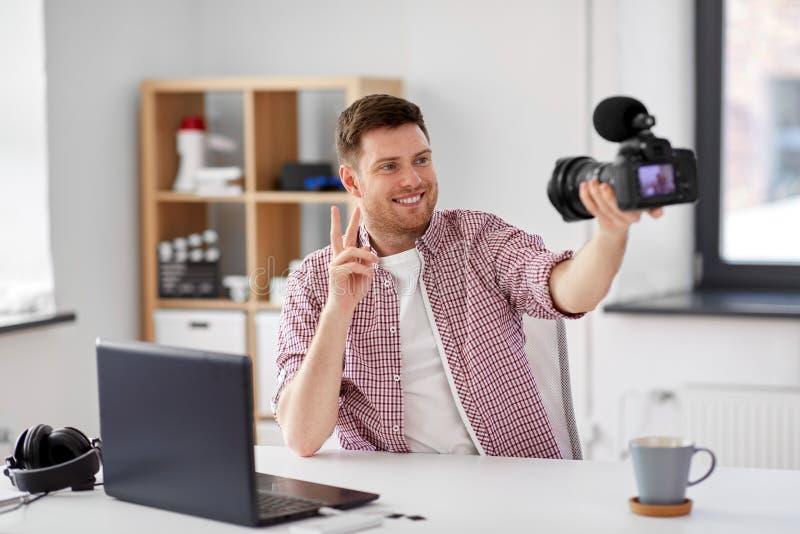 Blogger video masculino com c?mera que publica em blogs em casa imagem de stock royalty free