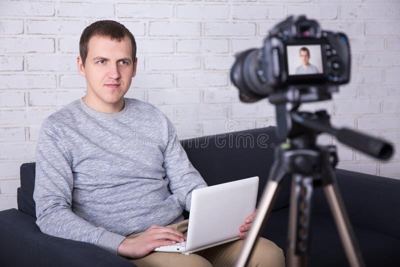 Blogger visuel de jeune homme enregistrant la nouvelle vidéo à la maison photo stock