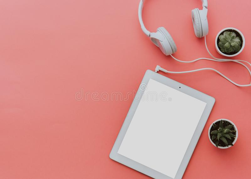 Blogger workspace with tablet and headphones on pastel background. Mock up, Flat lay, top view, minimalistic styled home office stock image