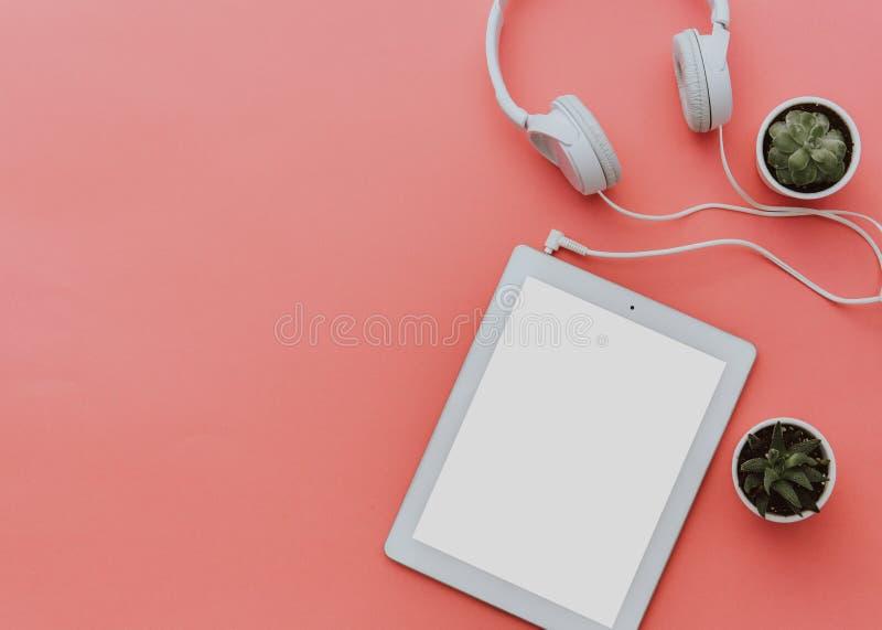 Bloggerarbeitsplatz mit Tablette und Kopfhörern auf Pastellhintergrund Verspotten Sie oben, Ebenenlage, Draufsicht, minimalistic  stockbild