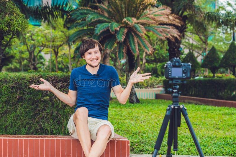 Bloggeren för den unga mannen antecknar videopn framme av kameran i parkera arkivfoto