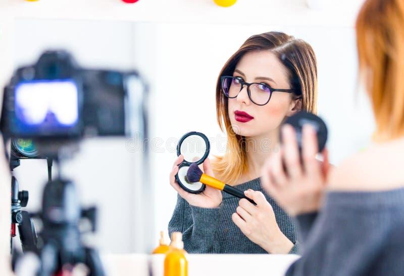 Bloggerfrau, die Kosmetik an der Kamera aufträgt stockfotografie
