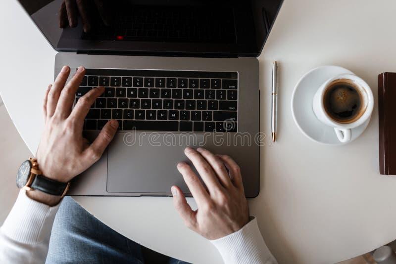Bloggergeschäftsmannkerl in T-Shirt Funktion auf einem modernen Laptop in einem hellen Büro Draufsicht über den weißen hölzernen  stockfotografie