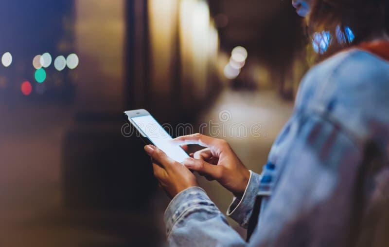 Bloggerhipster som använder i handgrejmobiltelefonen, kvinna med ryggsäcken som pekar fingret på smartphonen för tom skärm på bak fotografering för bildbyråer