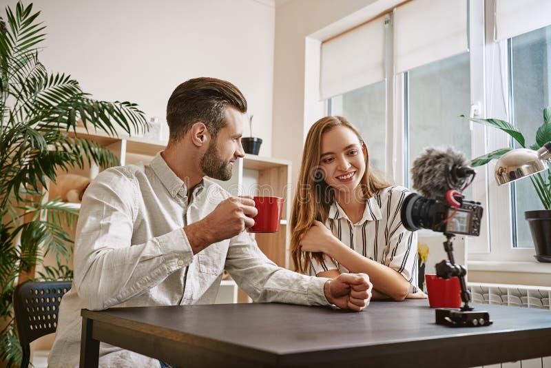 Bloggers bem sucedidos Bloggers de sorriso que bebem um chá ao fazer o índice novo para seu blogue imagem de stock
