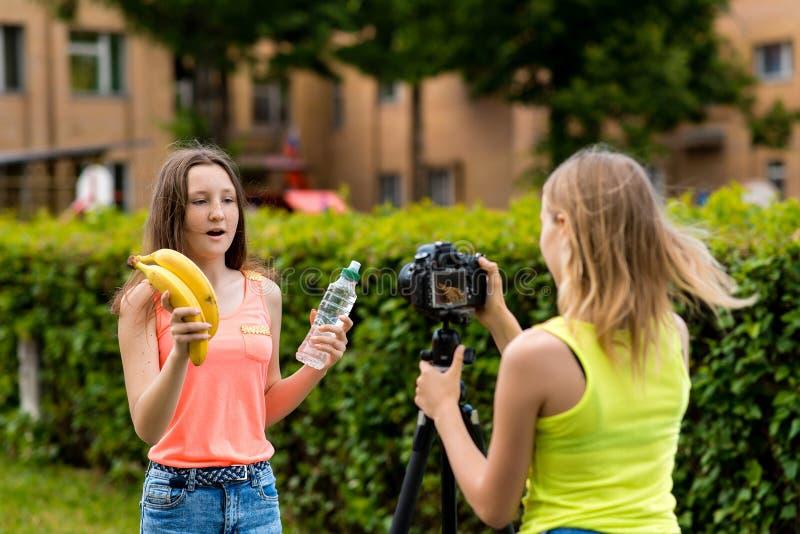 Bloggers de las chicas jóvenes, en verano en la ciudad en la naturaleza Vídeo de registro en la cámara En sus manos sostiene una  imagenes de archivo