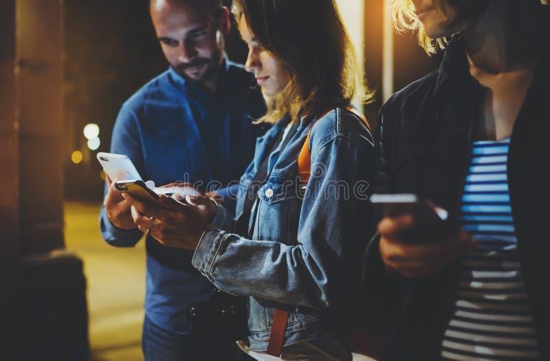 Bloggers die samen vinger op het schermsmartphone richten op achtergrond bokeh licht in nacht atmosferische stad, groepeert volwa royalty-vrije stock fotografie