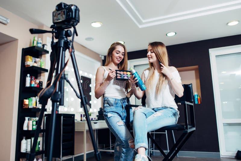 Bloggers fêmeas de sorriso da beleza que reveem produtos de composição para seu blogue que grava um vídeo na câmera no salão de b fotografia de stock
