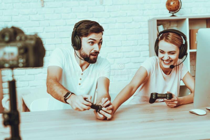 Bloggers que jogam um jogo de vídeo no console foto de stock
