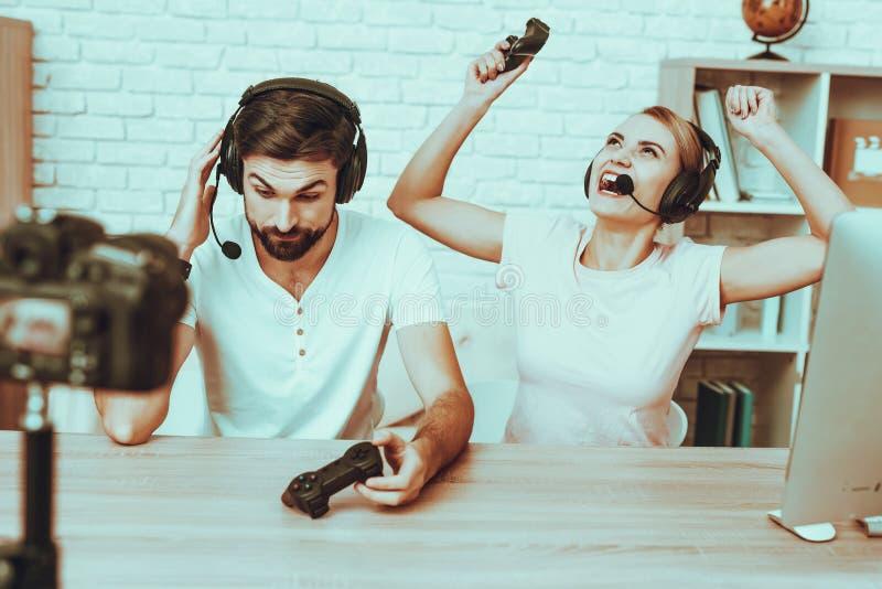 Bloggers que jogam um jogo de vídeo no console imagem de stock royalty free