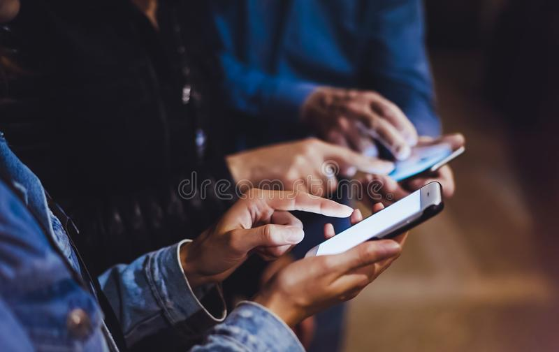 Bloggers together pointing finger on screen smartphone on background bokeh light in night atmospheric city, group adult hipsters f stock photography