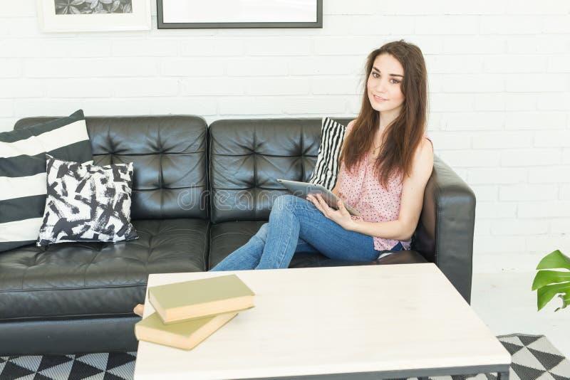 Blogging, μελέτη και έννοια ανθρώπων - νέα όμορφη γυναίκα που χρησιμοποιεί την ταμπλέτα στο σπίτι στοκ εικόνες
